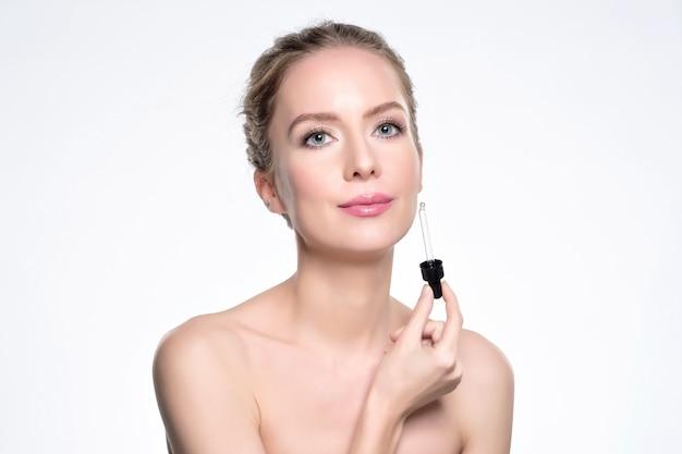 Beau Modèle Appliquant Un Traitement Cosmétique De Sérum De Peau Sur Blanc Photo Premium