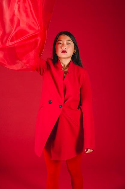 Beau modèle asiatique posant dans des vêtements rouges Photo gratuit