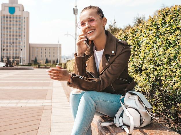 Beau Modèle Brune Souriante Vêtue D'une Veste Hipster D'été Et De Vêtements En Jeans Fille Branchée Assise Sur Le Banc Dans La Rue Femme Drôle Et Positive Parlant Au Téléphone Photo gratuit
