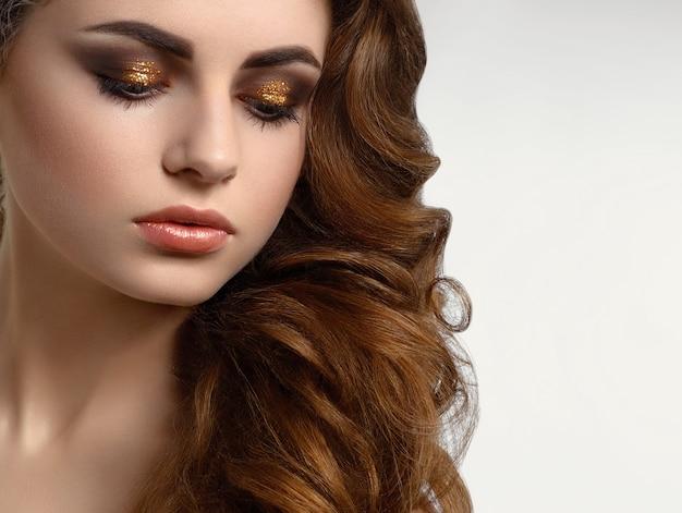 Beau modèle avec des cheveux bouclés bruns portant incroyable maquillage de soirée Photo Premium