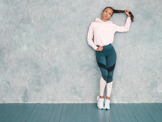 Beau Modèle Avec Un Corps Bronzé Parfait. Femme Posant En Studio Près Du Mur Gris. Tenant Ses Cheveux à La Main Photo gratuit