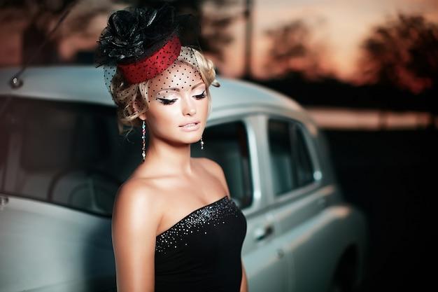 Beau Modèle De Fille Blonde Fashion Sexy Avec Maquillage Lumineux Et Coiffure Frisée Dans Un Style Rétro Assis Dans Une Vieille Voiture Photo gratuit