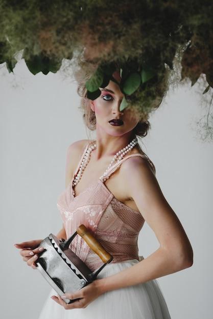 Beau modèle se dresse avec un vieux fer parmi de beaux bouquets dans la chambre Photo gratuit