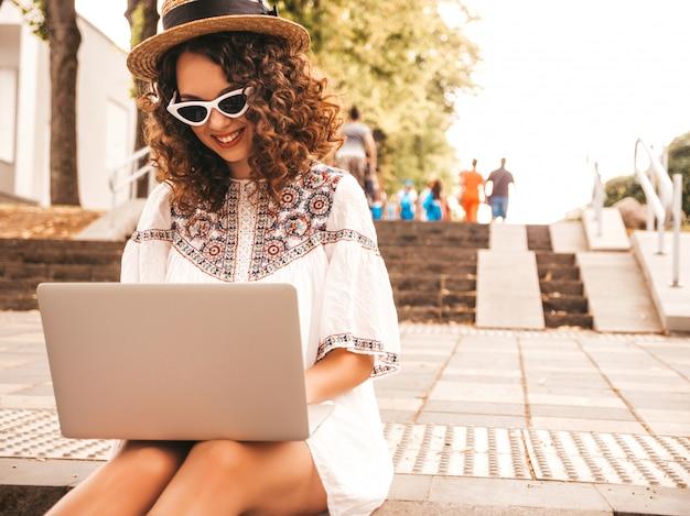 Beau Modèle Souriant Avec Une Coiffure De Boucles Afro Habillée En Robe Blanche D'été Hipster. Photo gratuit