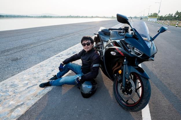 Beau motard avec casque dans les mains de la moto Photo gratuit