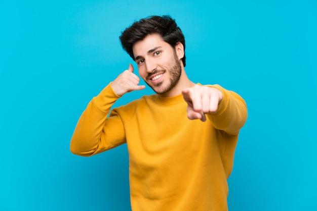 Beau sur mur bleu isolé, faisant un geste de téléphone et devant pointant Photo Premium