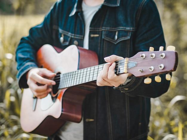 Beau musicien jouant de la guitare acoustique sur le champ d'herbe flou fond. Photo Premium