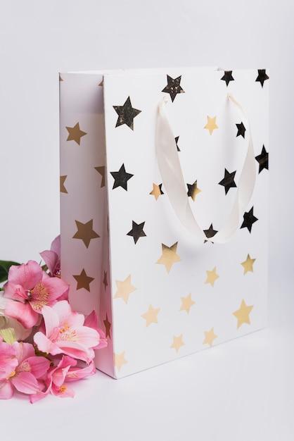 Beau nénuphar rose près du sac à provisions blanc avec une forme d'étoile dorée sur fond blanc Photo gratuit