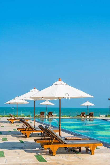 Beau parasol et chaise autour de la piscine de l'hôtel et du complexe Photo gratuit
