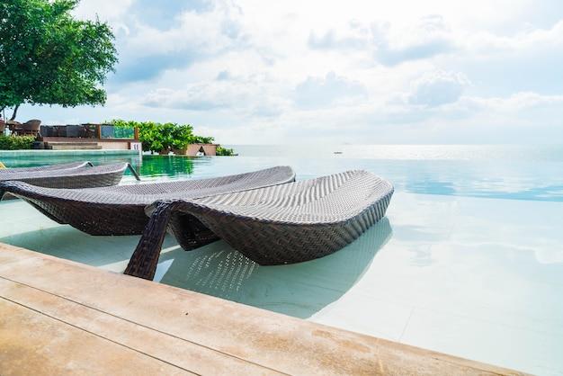 Beau parasol et chaise de luxe autour de la piscine extérieure de l'hôtel et du complexe Photo Premium
