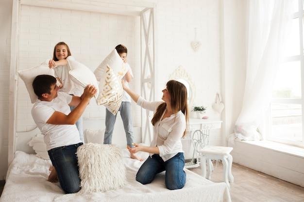 Beau parent avec leur enfant jouant bataille d'oreillers sur le lit dans la chambre Photo gratuit
