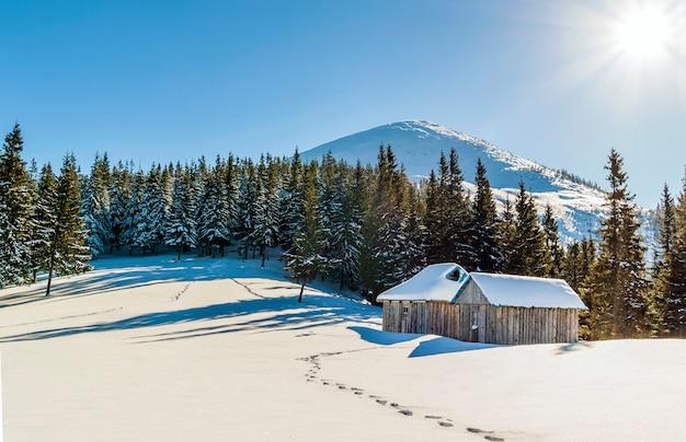 Beau paysage d'hiver dans les montagnes avec chemin de neige dans la steppe et petites maisonnettes Photo Premium