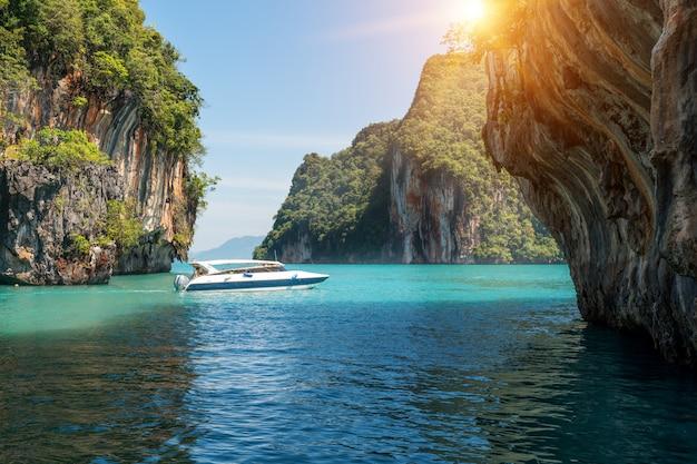 Beau paysage de montagne de roches et une mer cristalline avec la vitesse du bateau à phuket, en thaïlande. Photo Premium