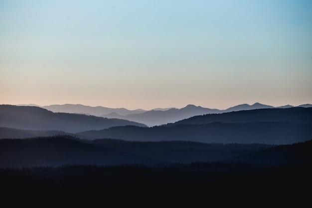 Beau Paysage De Montagnes Et De Collines Sous Un Ciel Rosé Photo gratuit