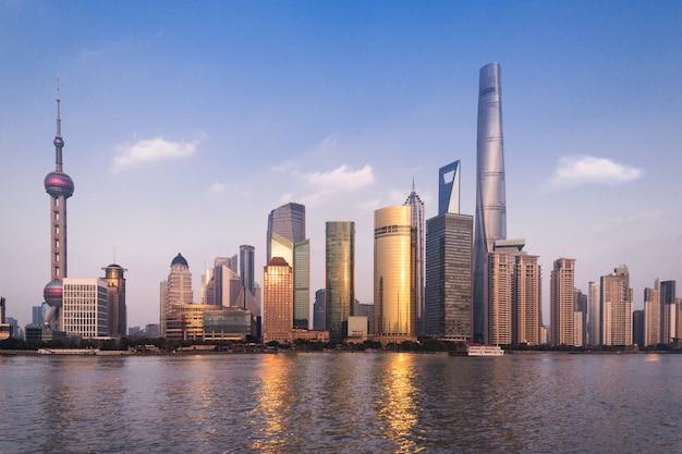 Beau paysage urbain avec des gratte-ciel de verre debout le long de la rivière dans le contexte du soleil couchant Photo Premium