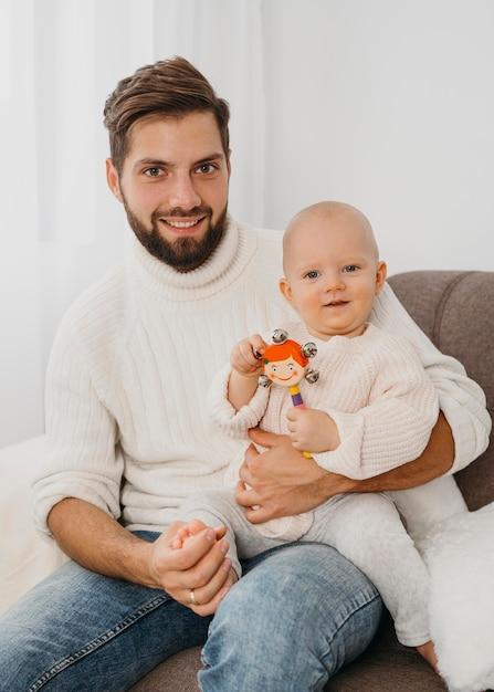 Beau Père Posant Sur Le Canapé Avec Bébé Photo gratuit