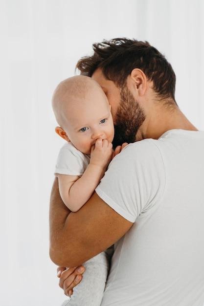 Beau Père Tenant Et Embrassant Son Bébé Photo gratuit