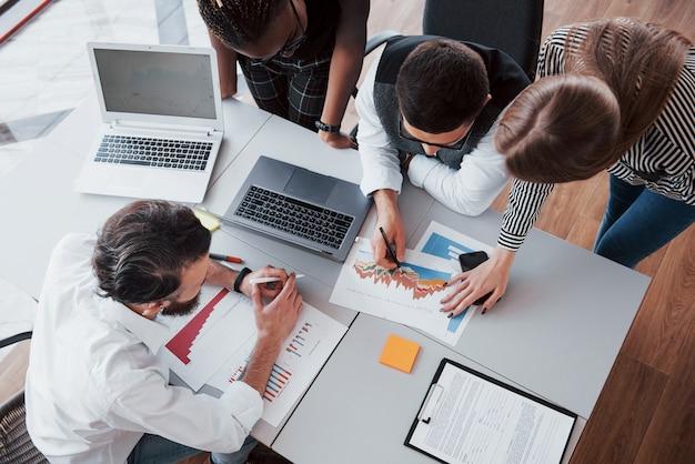 Beau personnel élégant assis dans le bureau au bureau à l'aide d'un ordinateur portable et à l'écoute d'un collègue. Photo gratuit