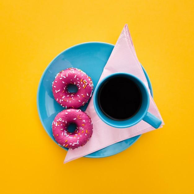 Beau petit déjeuner avec beignet et tasse de café sur jaune Photo gratuit