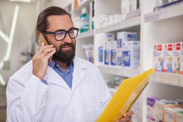 Beau pharmacien mature répondant aux appels, travaillant à la pharmacie Photo Premium
