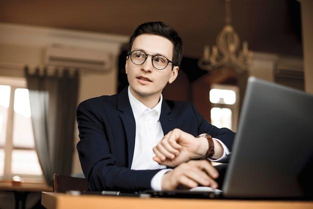 Beau Pigiste Caucasien Parlant Avec Quelqu'un Assis à Son Bureau Et Regardant Sa Montre. Photo Premium