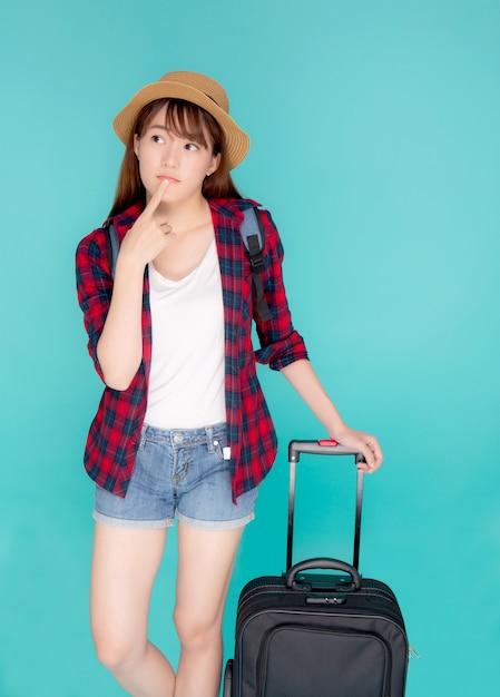 Beau Portrait Jeune Femme Asiatique Pense Idée Voyage En Vacances Avec Des Bagages Isolé Sur Fond Bleu. Photo Premium