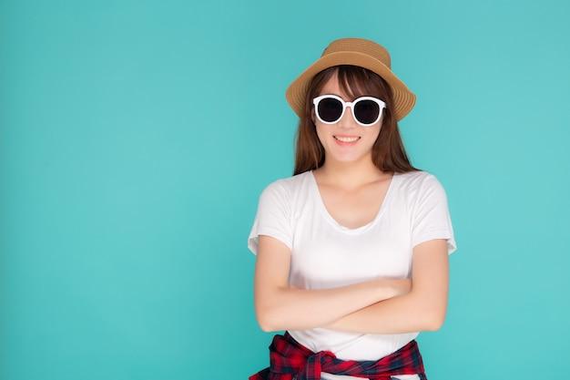 Beau Portrait Jeune Femme Asiatique Porter Chapeau Et Lunettes De Soleil Souriant Expression Confiant Profiter De L'été En Vacances Isolé Sur Fond Bleu. Photo Premium