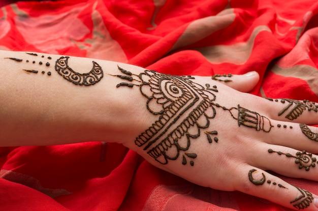 Beau tatouage de mehndi sur la main de la femme placée sur du textile rouge Photo gratuit