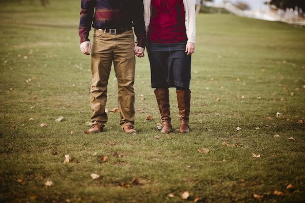 Beau Tir D'un Couple Se Tenant La Main En Se Tenant Debout Dans Un Champ Herbeux Avec Un Arrière-plan Flou Photo gratuit