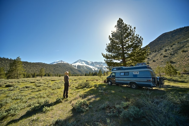 Beau Tir D'une Femme Debout Sur Un Terrain Herbeux Près D'une Camionnette Avec Montagne Photo gratuit
