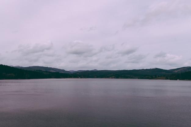 Beau Tir D'un Lac Avec Des Collines à L'horizon Et Un Ciel Nuageux Photo gratuit