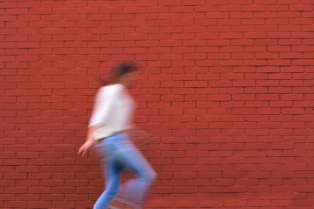 Beau Tir D'un Mur De Pierre Rouge Et Un Contour D'une Jeune Fille En Vêtements Décontractés Photo gratuit