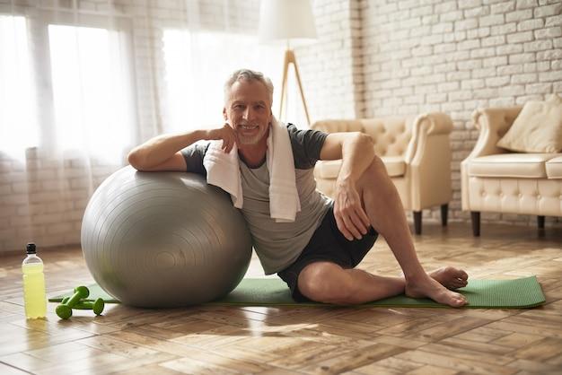 Beau vieil homme fait la séance d'entraînement pilates à la maison. Photo Premium