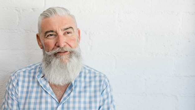 Beau vieillard barbu en chemise en studio Photo gratuit