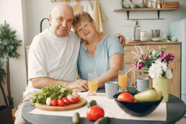 Beau vieux couple prépare des plats dans une cuisine Photo gratuit