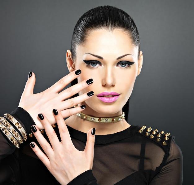Beau Visage De Femme Fashion Avec Des Ongles Noirs Et Un Maquillage Lumineux. Fille élégante Sexy Avec Des épines De Bracelet Sur Le Cou Photo gratuit