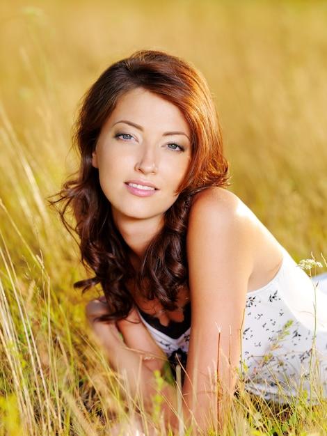 Beau Visage De La Jeune Femme Sexy Posant Allongé Sur L'herbe Photo gratuit