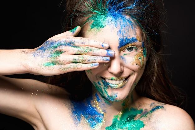 Beau visage avec de la peinture colorée sur fond noir Photo Premium
