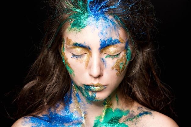 Beau visage avec de la peinture colorée sur un fond noir Photo Premium