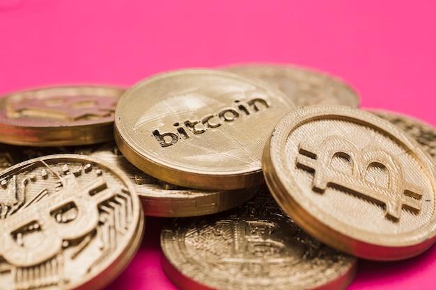 Beaucoup de bitcoins sur fond rose Photo gratuit