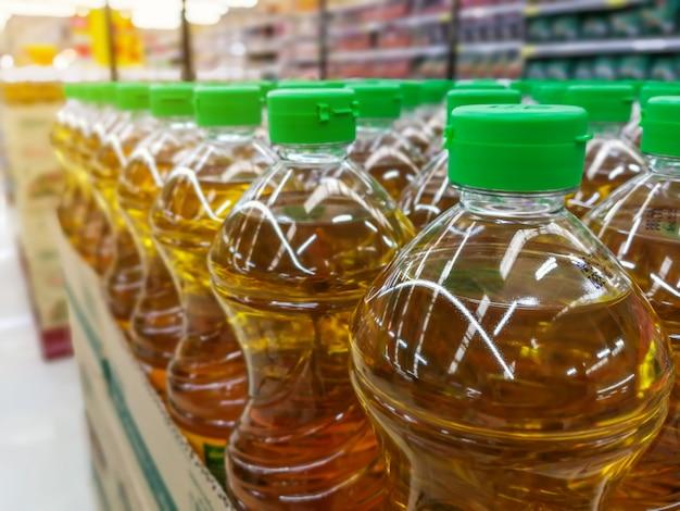 Beaucoup de bouteilles en rangée pile d'huile végétale sur les étagères dans les matériaux de supermarché Photo Premium