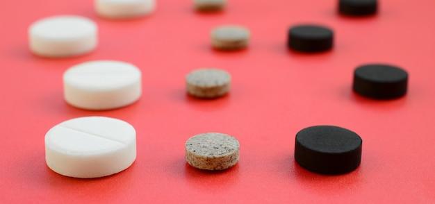 Beaucoup de comprimés blancs, noirs et bruns se trouvent sur la surface rouge. Photo Premium