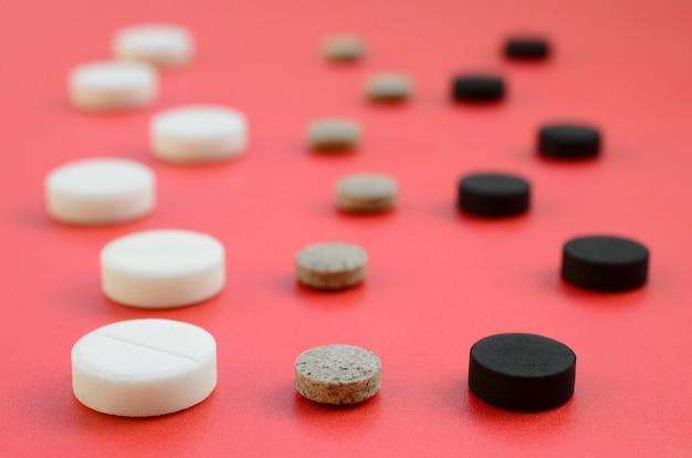 Beaucoup de comprimés blancs, noirs et marron se trouvent sur la surface rouge Photo Premium