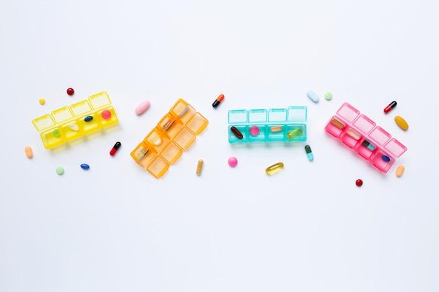 Beaucoup de comprimés colorés et de capsules avec boîte à pilules isolé sur blanc Photo Premium