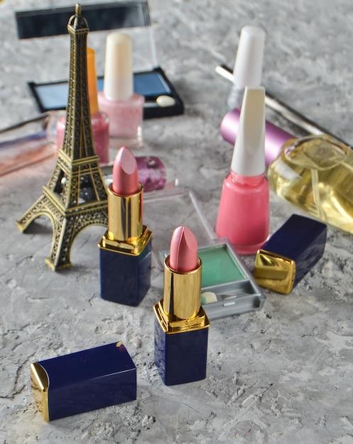 Beaucoup De Cosmétiques Féminins Pour Le Maquillage Et Les Soins De Beauté. Vernis à Ongles, Flacon De Parfum, Ombres à Maquillage, Rouge à Lèvres, Une Statuette De La Tour Eiffel. Photo Premium