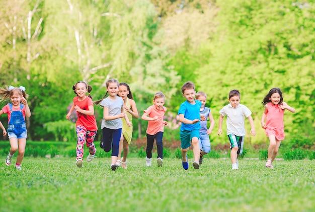 Beaucoup D'enfants, De Garçons Et De Filles Différents Qui Courent Dans Le Parc Le Jour D'été Ensoleillé Dans Des Vêtements Décontractés Photo Premium