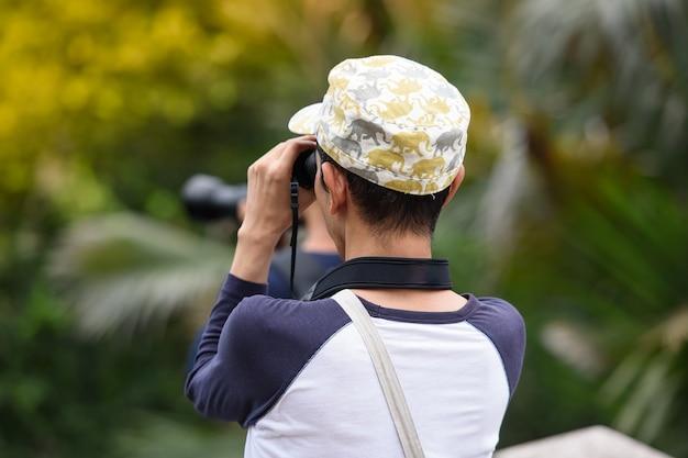 Beaucoup de gens utilisent des caméras pour faire briller quelque chose dans le parc. Photo Premium