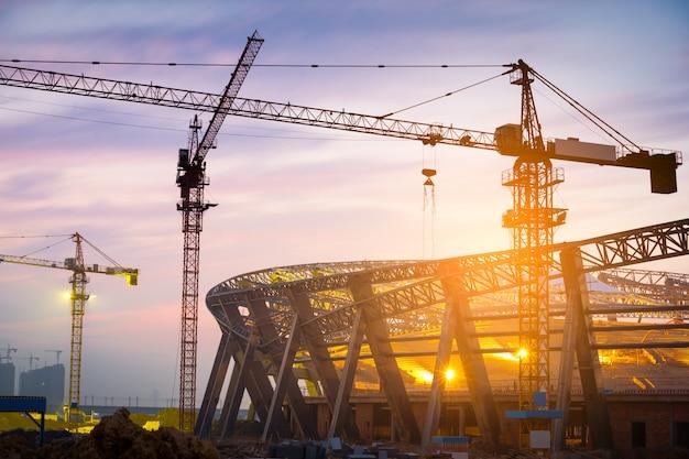 Beaucoup de grues à tour construisent de grands bâtiments résidentiels la nuit. Photo Premium