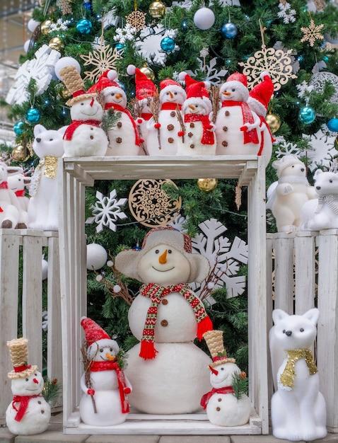 Beaucoup de jouets bonhommes de neige, cerfs, ours et renards, debout sous l'arbre, jouets de noël, Photo Premium