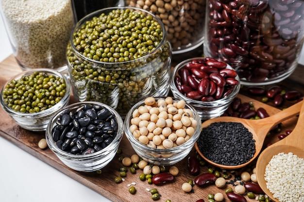 Beaucoup de noix et de graines de sésame sur un plancher en bois. Photo Premium